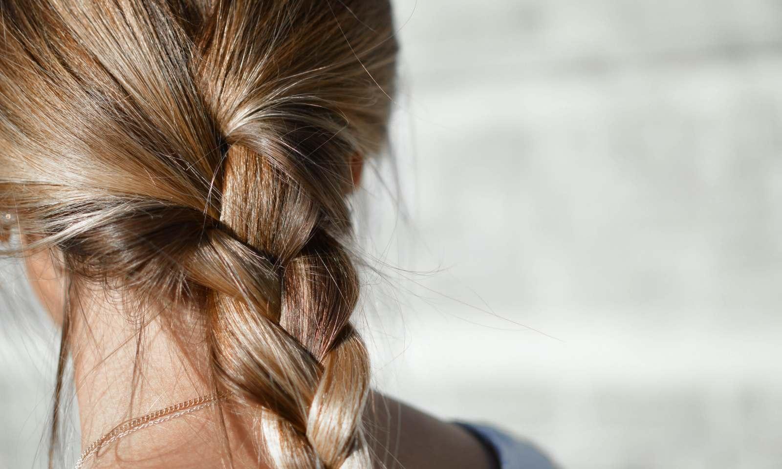 ragazza con capelli fini biondi legati in una treccia