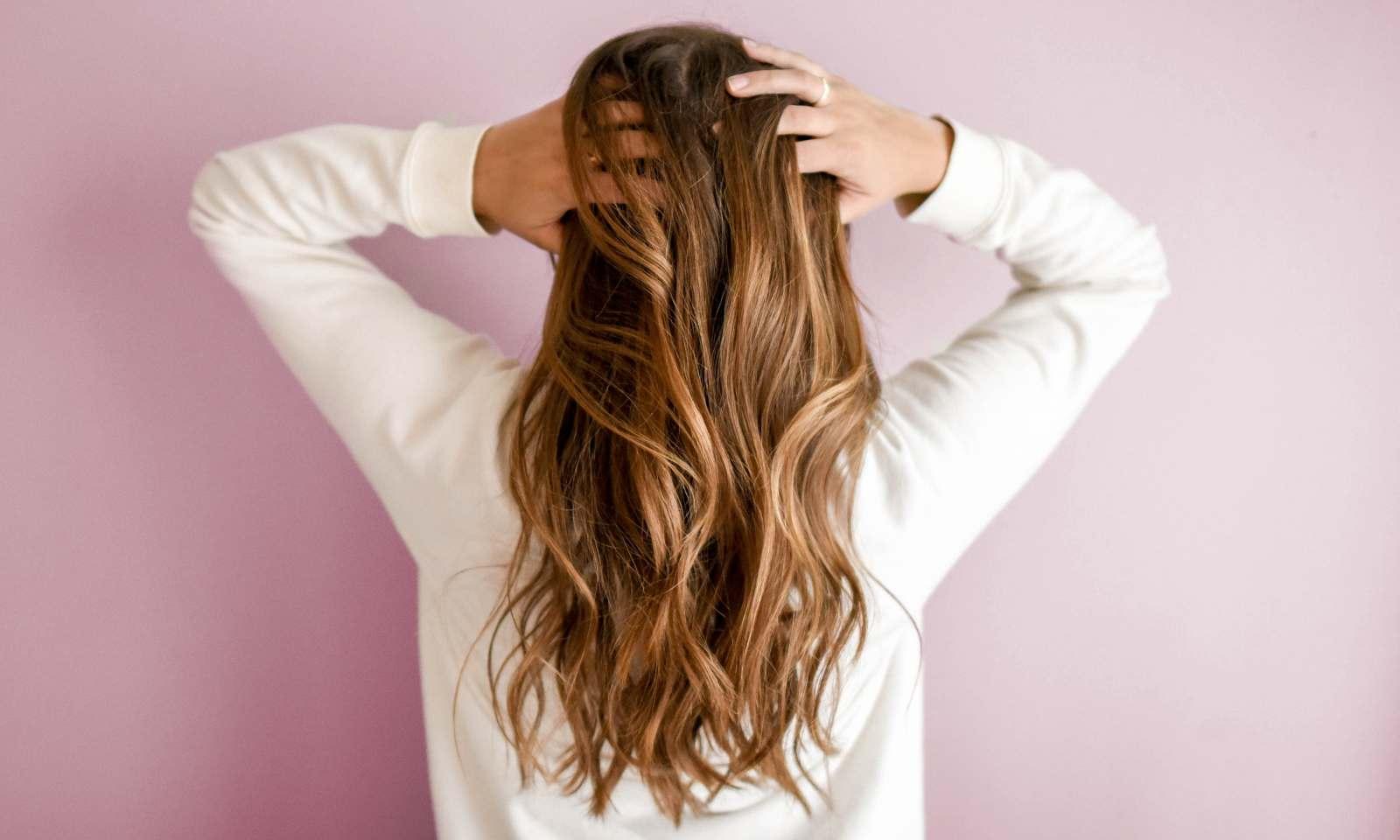 ragazza con capelli lunghi ondulati castano chiaro di spalle si tocca i capelli