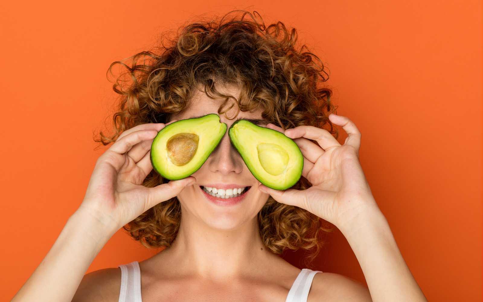 ragazza con capelli ricci tiene in mano un avocado aperto a metà
