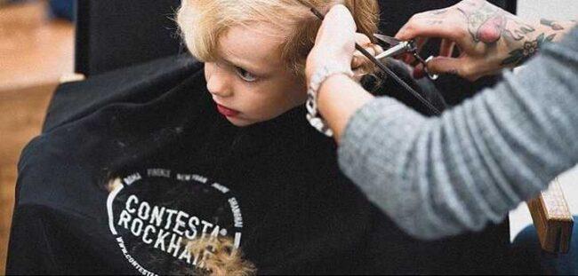 bambino biondo si taglia i capelli dal parrucchiere
