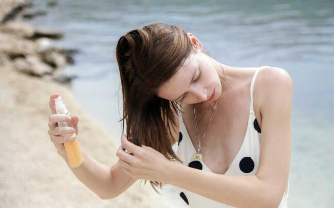 ragazza al mare spruzza prodotto per capelli