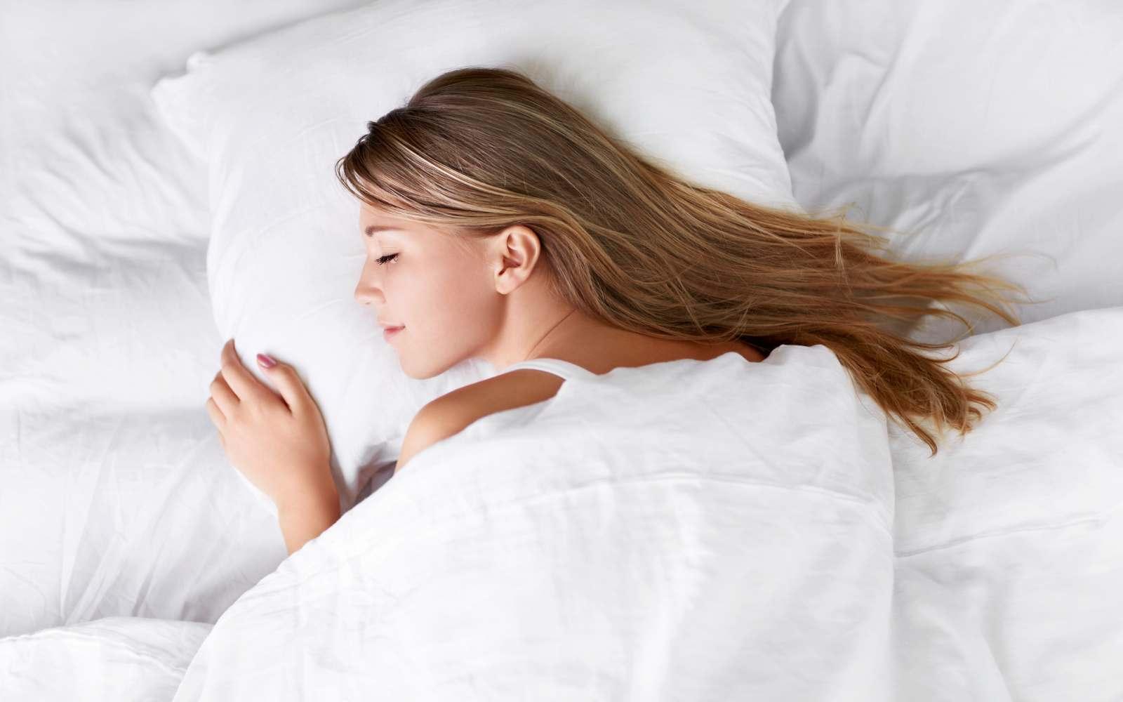 ragazza con capelli lunghi biondo scuro dorme su letto con lenzuola bianche