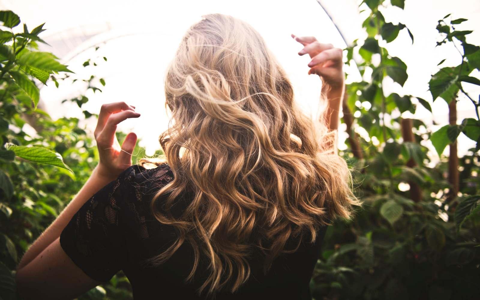 ragazza con capelli biondi ondulati di spalle con maglia a maniche corte nera, tra piante verdi