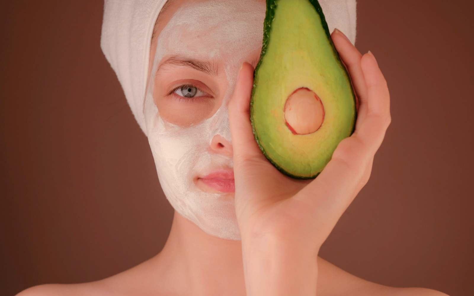 ragazza con avocado, maschera per viso bianca e turbante bianco con maschera per capelli all'avocado