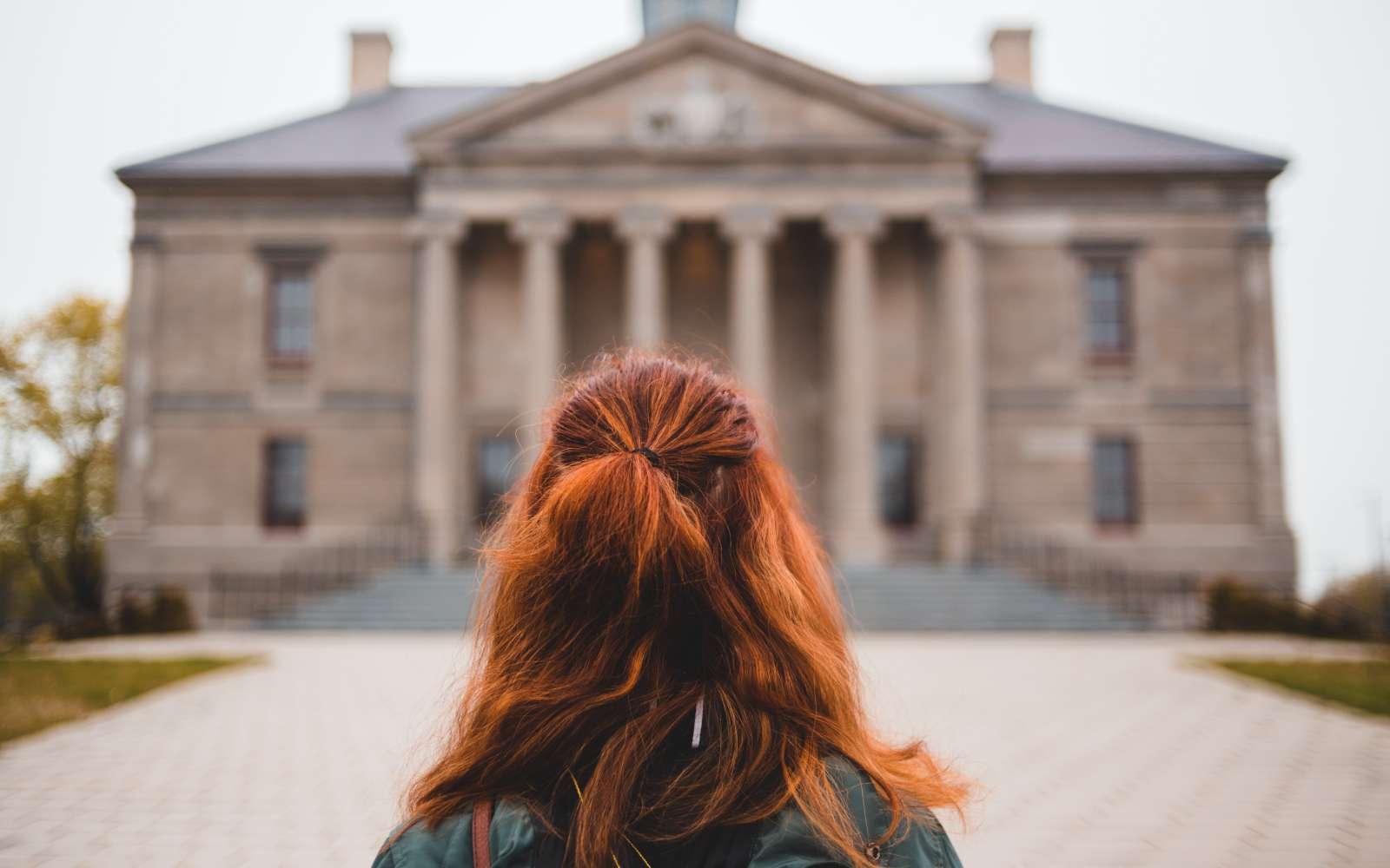 ragazza di spalle con capelli rossi crespi legati con mezza coda