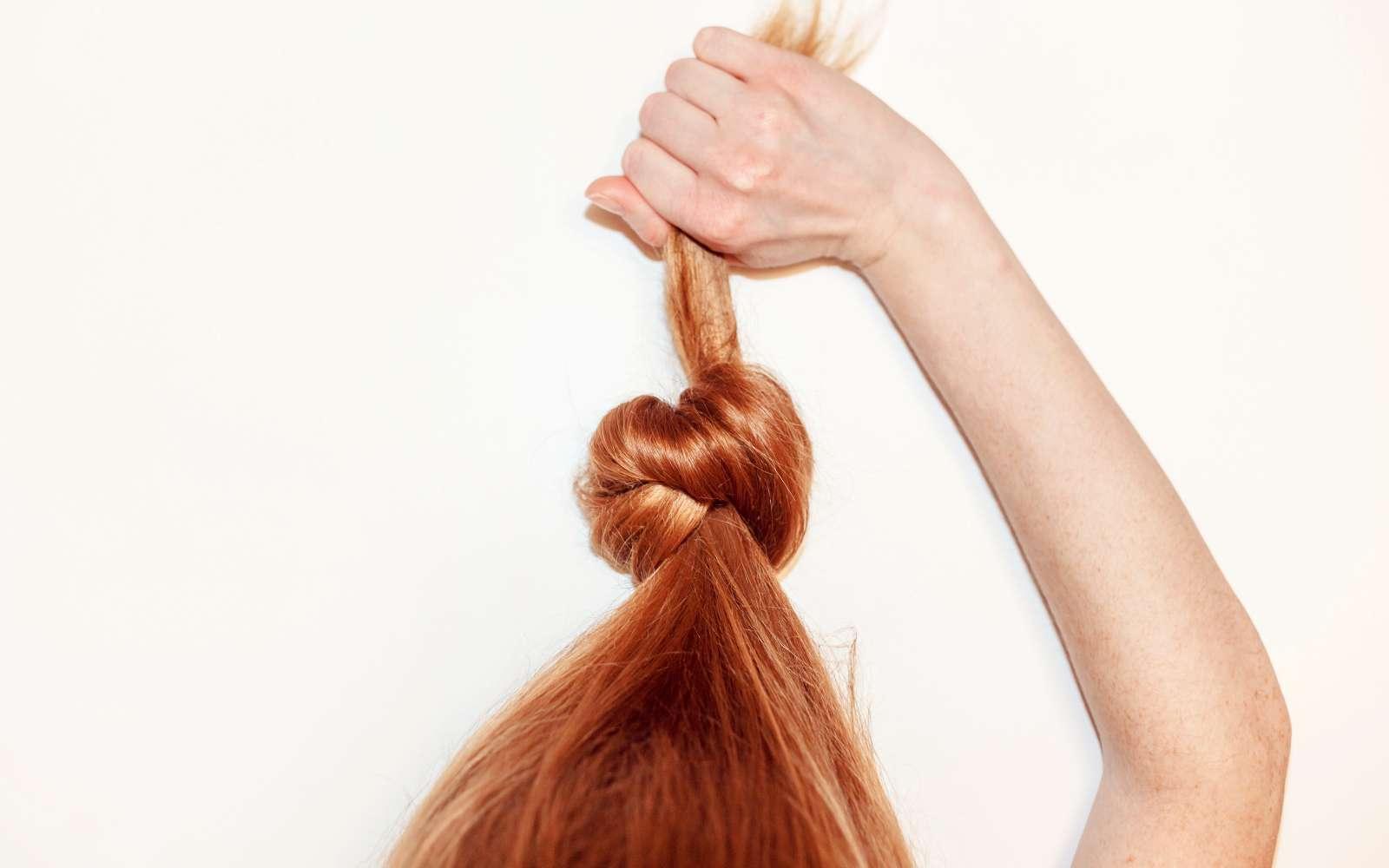 capelli rossi legati tirati verso l'alto dalla mano della ragazza