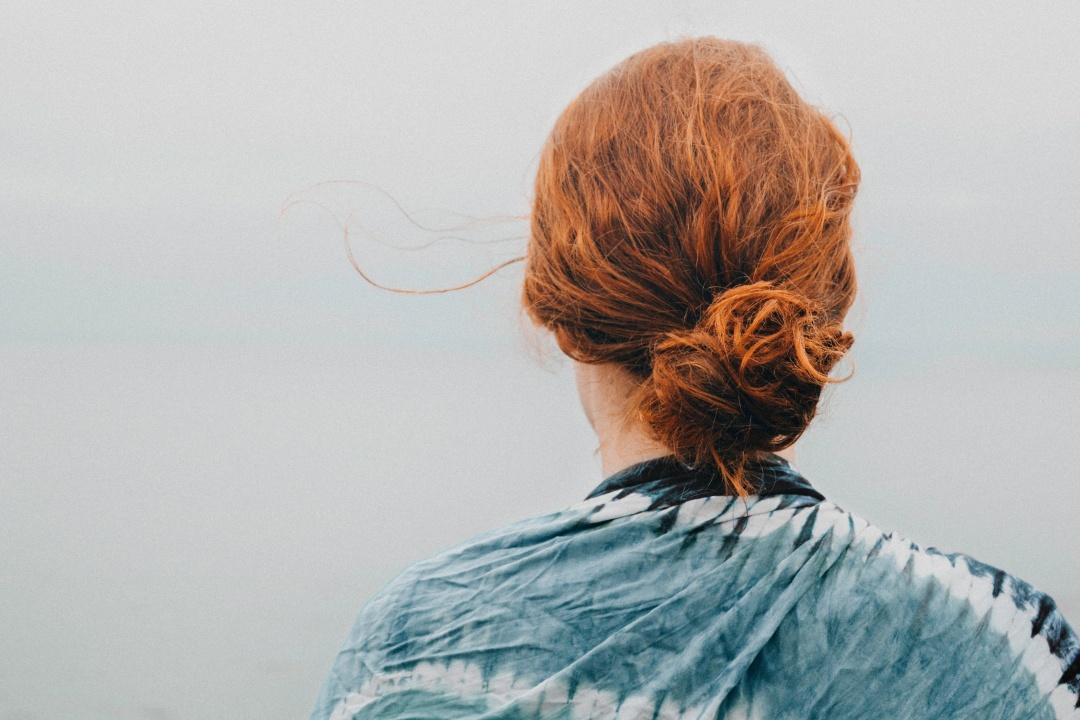 ragazza di spalle con capelli rossi legati crespi
