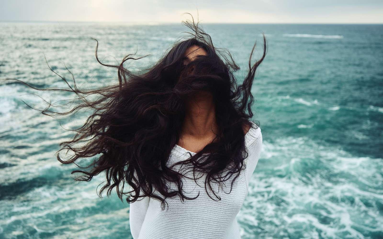 ragazza mora al mare con capelli rovinati al vento