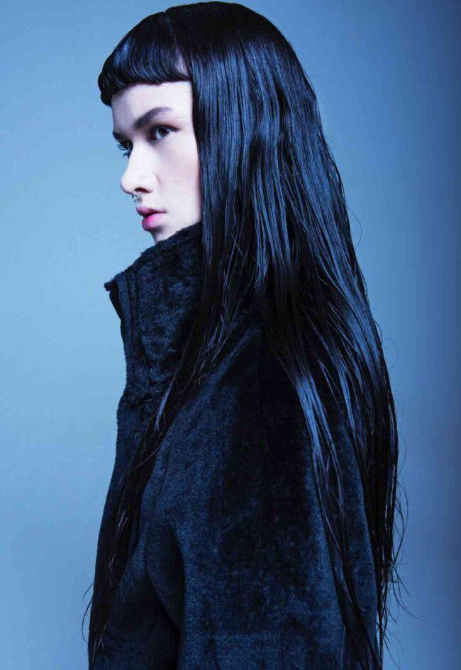 ragazza di profilo mora con frangella, capelli lunghi e viso allungato